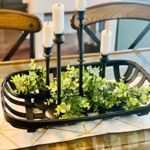 dining room centerpiece with black candlesticks, black basket and greenery