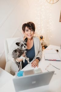 friendly interior designer holding a small dog in her office